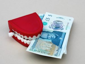 Red teeth holding money at the Glasgow orthodontics clinic.