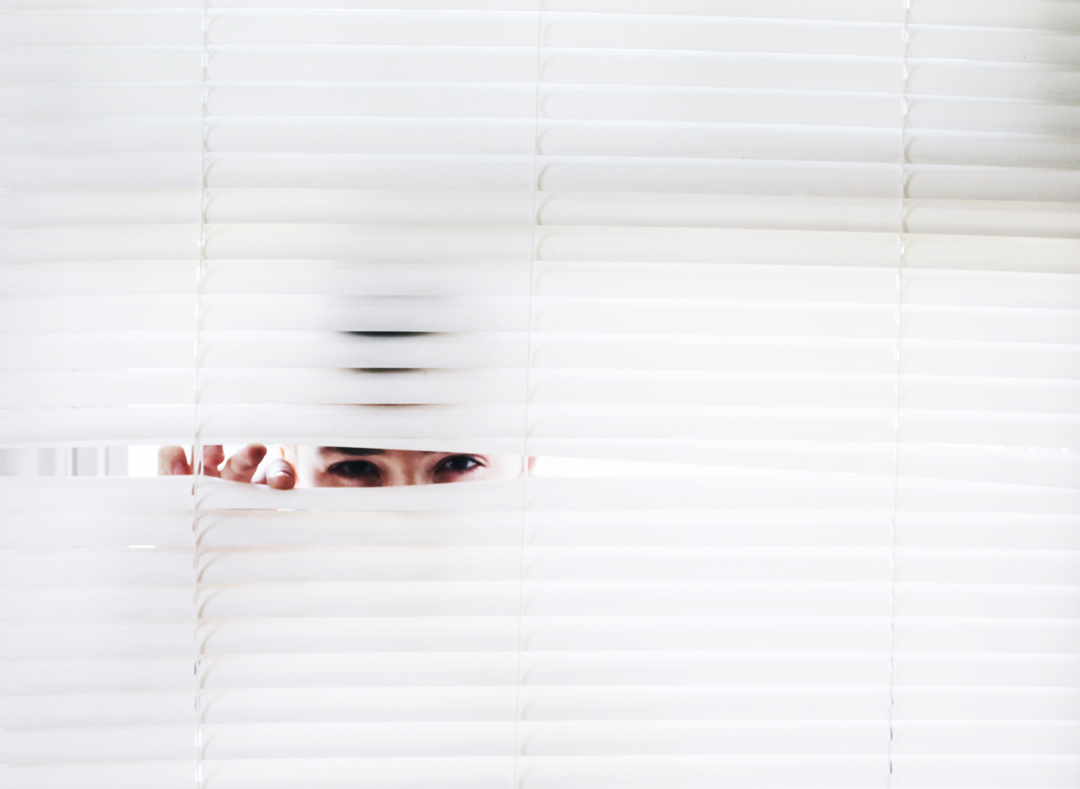 Person peeking through their window blinds in Glasgow.