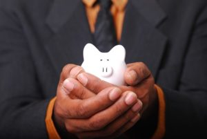 how insulation helps you save moneyman holding piggy bank