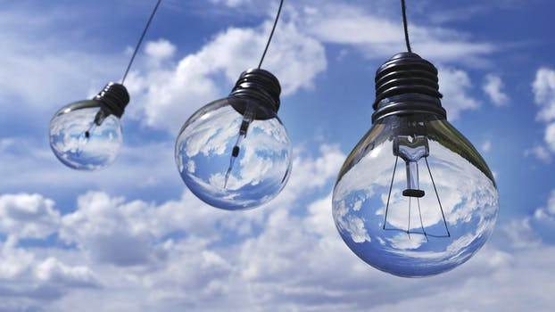 Artwork of three light bulbs hanging from a blue sky with white clouds to represent energy saving lighting.