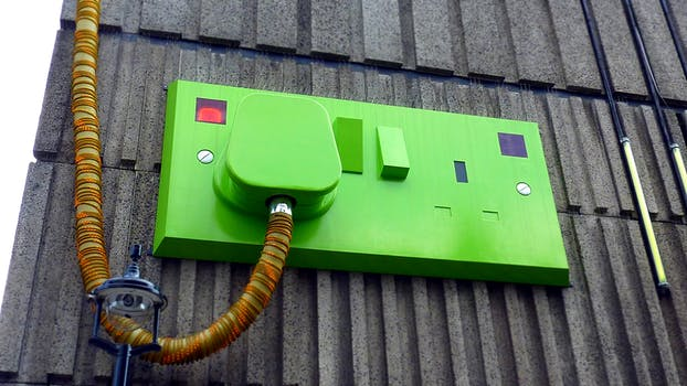 Large green plug and socket artwork on the side of a building to represent energy saving lighting.